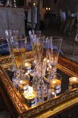 Glasses of sparkling wine and tealights on mirror