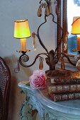Light and antique books on side table