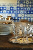 Antique glasses on tray, stack of plates, cutlery