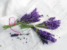 Three bunches of fresh lavender on a linen cloth