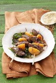 Lamb kebabs with sesame seeds and spinach