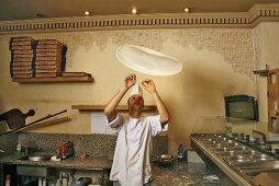 Italian pizza baker throwing dough into the air