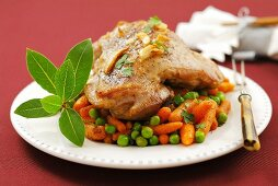 Piece of turkey leg on carrots and peas (Christmas)