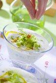 Sprinkling walnuts on tarator (Bulgarian yoghurt & cucumber soup)