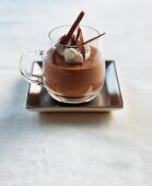 Mousse au chocolate with a dollop of cream and chocolate curls