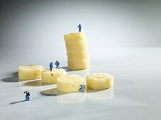 Astronaut figures inspecting hard cheese