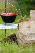A cooking pot and a paper bag of coal