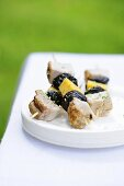 Pork kebabs with dried plums and cheese