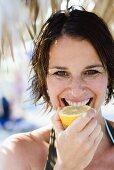 Woman biting into a lemon