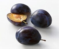 Two whole and one halved plum (variety: Bluefree)