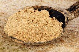 Amchur (mango powder) in wooden spoon