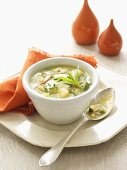 Vegetable soup (peas, courgettes, potatoes) with bacon