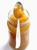 Peach and mango jam in jar with spoon