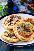 Four small pizzas topped with tomatoes, capers, olives & cheese