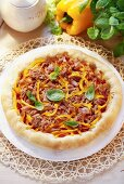 A round pizza topped with tuna, peppers and basil