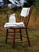 Towels and a jug of water on a wooden chair out of doors