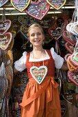 Woman in dirndl by stall selling Lebkuchen hearts (Oktoberfest)