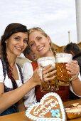 Two women clinking full tankards of beer (Oktoberfest, Munich)