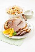 Roast pork with orange wedges, cabbage salad