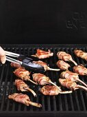 Bacon-wrapped lamb chops on a barbecue