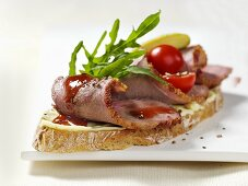Open sandwich of duck breast, rocket and cocktail tomatoes