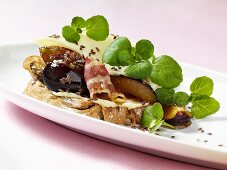 Fried bacon, plums and linseed on bread