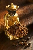 Gilded statuette with a bowl of ground coffee, coffee beans