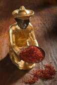 Gilded statuette with a bowl of saffron threads