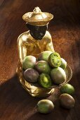 Gilded statuette with a bowl of baby kiwis