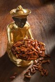 Gilded statuette with small dried chillies