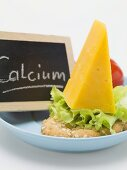 Cheddar cheese on cracker, slate board with the word Calcium