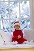 Little girl in Santa costume sitting by window