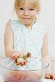 Little girl dyeing Easter egg