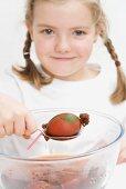 Little girl dyeing Easter eggs