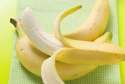 Three bananas on green background