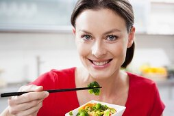 Woman eating Asian vegetables
