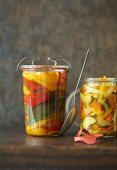 Pickled courgettes and peppers in oil, a jar of each