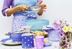 Woman sieving flour into a bowl, crockery & eggs in front