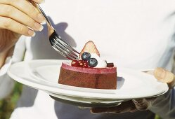 Woman eating small chocolate cake topped with berry mousse