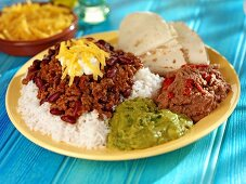 Chili con carne on rice with tortilla and two sauces