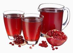 Pomegranate juice in jug & two glasses, fresh pomegranate
