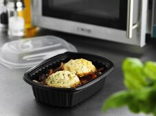 Beef stew in plastic container in front of microwave oven