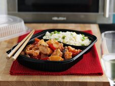 Chinese ready-meal in front of microwave oven