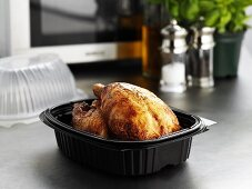 Take-away roast chicken in plastic container in front of microwave