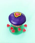 Muffin with purple icing and heart-shaped jelly sweets