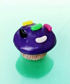 Muffin with purple icing and jelly beans
