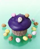 Muffin with purple icing and chocolate eggs