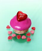 Muffin with pink icing, chocolate heart, heart-shaped jelly sweets