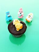 Muffin with chocolate icing and jelly chick for Easter