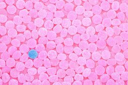One blue jelly tot surrounded by pink ones